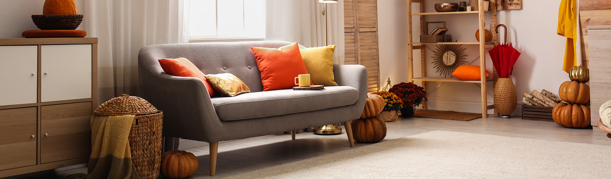 photo showing a rustic, fall decorated living space with a grey couch, light wood furniture accents, and orange pumpkins.