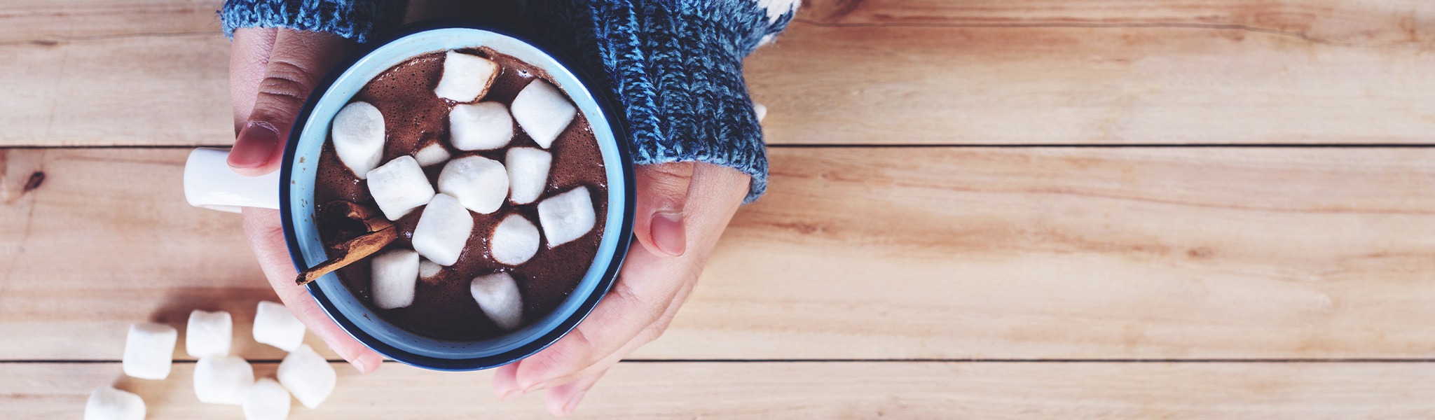 photo of a cup of hot coco being held by hands