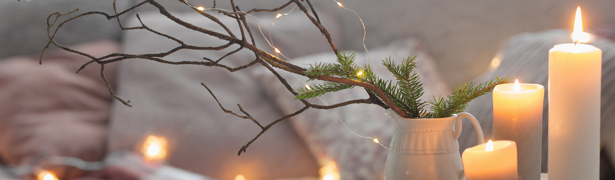 winter decor featuring multi sized candles and a white vase with lit up small branches