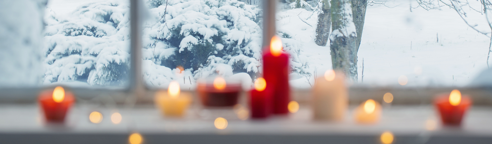 photo depicting candles lit in front of a wintery window